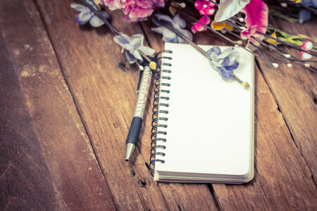 flower arrangements: Flowers and a notepad on a desk Stock Photo