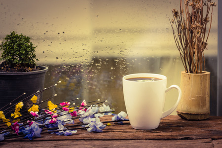 coffee mugs: Steaming coffee cup on a rainy day window background Stock Photo