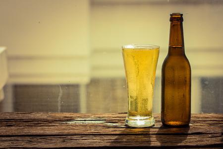 ボトルとガラス木製テーブルの上のビール 写真素材