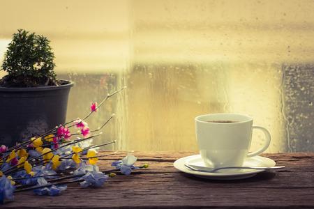 kropla deszczu: Parującą filiżankę kawy w deszczowy dzień tle okna
