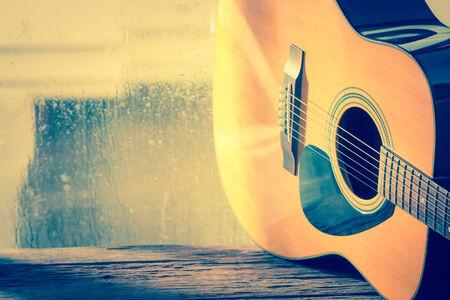 guitarra acustica: Guitarra acústica junto a la ventana con la gota de agua Foto de archivo