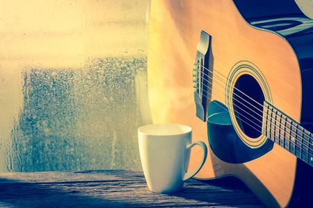 コーヒー カップとアコースティック ギター ドロップでウィンドウが次に水 写真素材