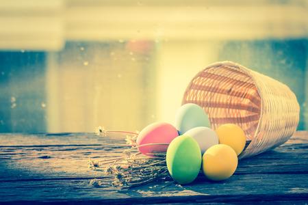 木製の背景の色のバスケットでイースターの卵 写真素材