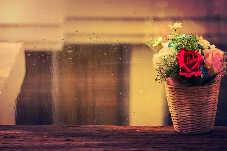 Flowers decoration on wood table beside glass window photo