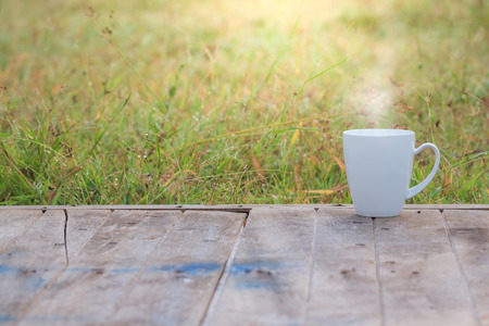 Steaming coffee cup on wood table. grass background Stock fotó