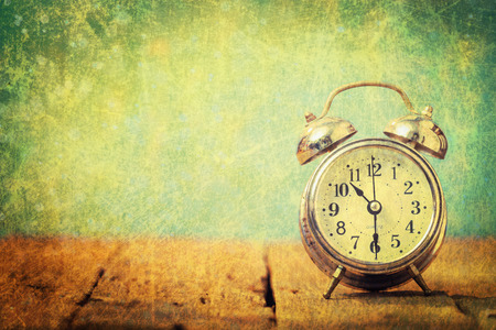 Vintage background with retro alarm clock on table.Vintage filter