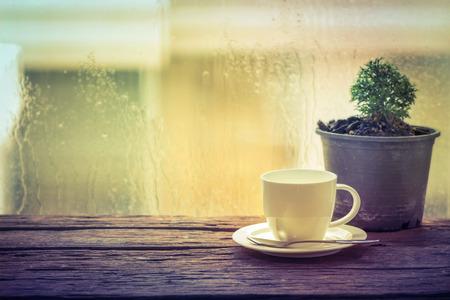 雨の日のウィンドウの背景にコーヒー カップ 写真素材