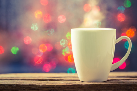 vapour: Steaming cup of coffee over a cityscape background Stock Photo