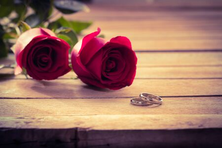 Couple ring with red rose on wood table photo
