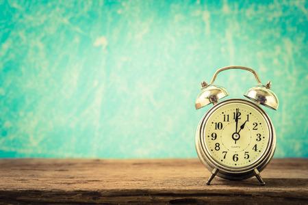 Fondo de la vendimia con el reloj de alarma retro en la mesa