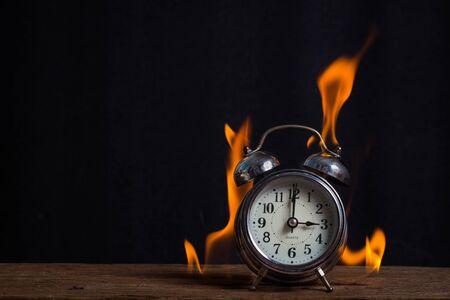engulfed: alarm flame on wood table Stock Photo