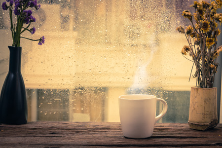 Steaming coffee cup on a rainy day window background Standard-Bild