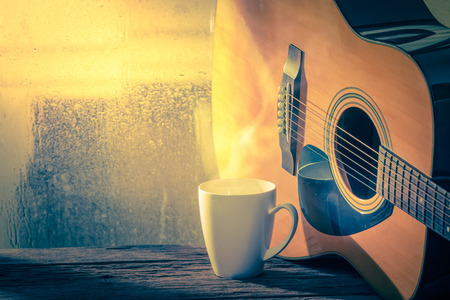 Acoustic guitar next the window with drop water Stock Photo