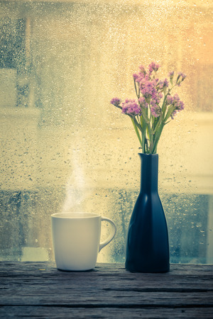 Steaming coffee cup on a rainy day window background Banco de Imagens