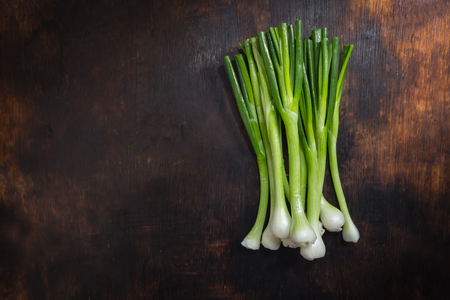 Still life with fresh scallions on a wooden board.