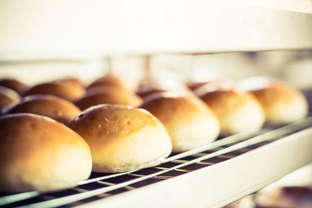 Leckere Brötchen mit Kruste auf verschwommen Bäckerei Innen Hintergrund.