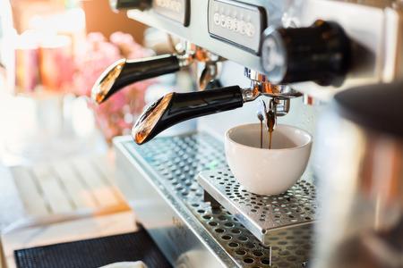 Professionelle Kaffeemaschine mit weißen Tasse und gießt Getränk Standard-Bild - 53586050
