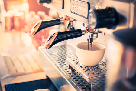 Professional coffee machine with white cup and pouring drink