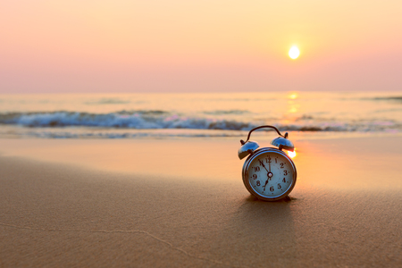 Alarm clock vintage with sunrise on beach Stockfoto