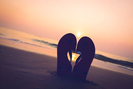 tilted: Silhouette slippers is tilted of love on  sandy ocean and sunset  or sunrise beach