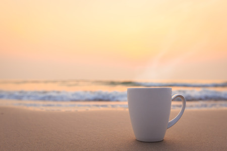 Close up white coffee cup on sand beach and view of sunset or sunrise background,peaceful Standard-Bild