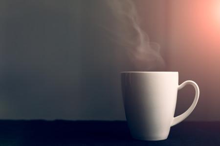 la taza blanca con líquido caliente y vapor de agua en el fondo