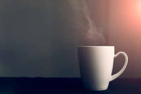 white cup with hot liquid and steam on background Stock Photo