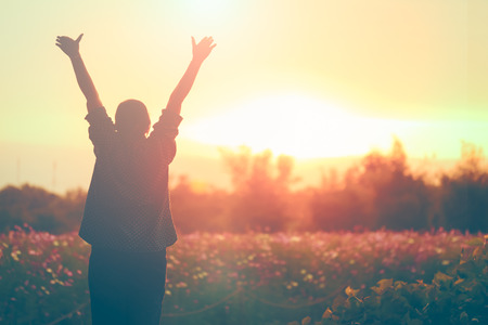 arms  outstretched: cheering woman open arms at sunrise flowers garden,Nature of Life Stock Photo