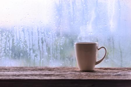 雨の日のウィンドウの背景色のコーヒー カップ
