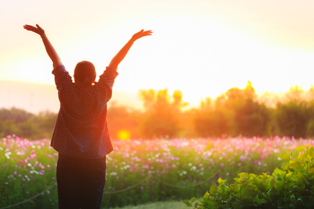 cheering woman open arms at sunrise flowers garden,Nature of Life