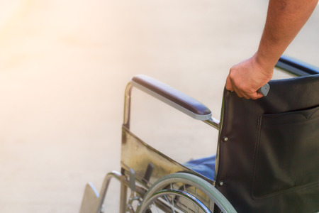 disablement: Empty wheelchair pushed by nurses hands