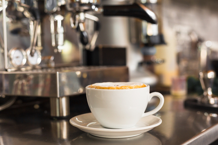 steel. milk: A cup of cappuccino coffee on bar counter