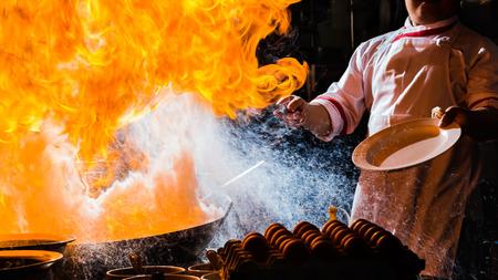 Feuerbrand ist das Kochen auf Eisenpfanne, umrühren Feuer sehr heiß Standard-Bild - 71392427