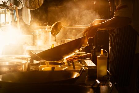 シェフは中華鍋で野菜を攪拌します。