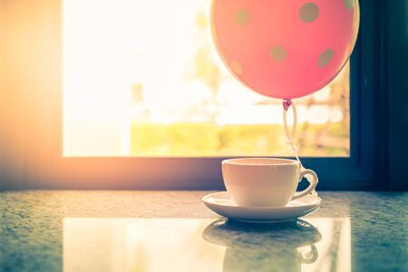 Coffee cup with balloon in front the window
