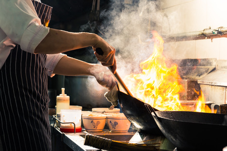 Chef is stirring vegetables in wok Foto de archivo