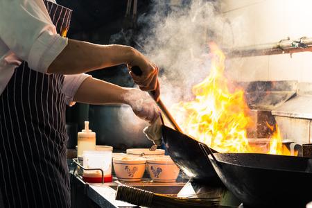 Chef is stirring vegetables in wok Standard-Bild