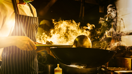 Chef is stirring vegetables in wok Stock Photo
