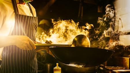 Chef is stirring vegetables in wok Reklamní fotografie - 81611080