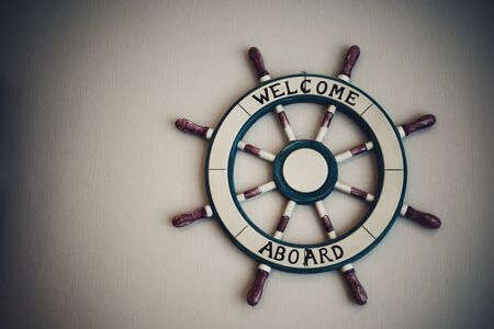 Steering wheel at wall background. Skipper's wheel for welcome