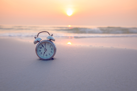 Alarm clock vintage with sunrise on beach Stok Fotoğraf