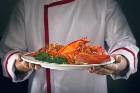Servido sosteniendo una langosta en manos chef
