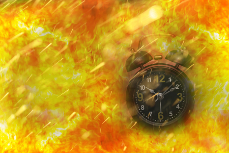 Alarm clock is on big fire flames are coming from it: time is burning
