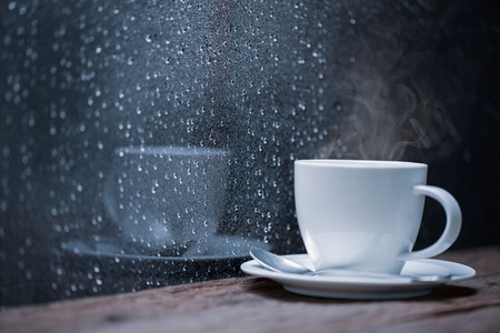 Coffee cup beside glass with the rain