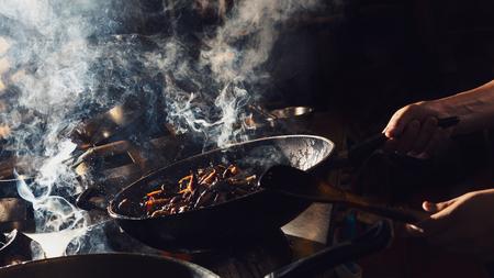 Chef is stirring vegetable in wok