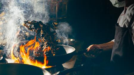 Chef está revolviendo verduras en wok
