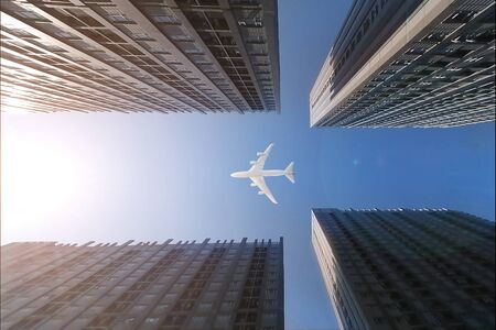 Airplane flying over business skyscrapers, high-rise buildings. transportation on blue sky.