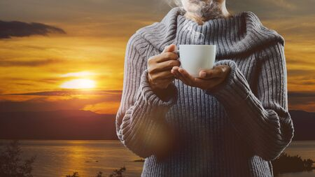 Holding white cup of coffee with sunrise