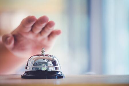 Bell on counter for service with hand. Ring the bell