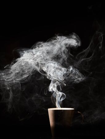 Steaming coffee cup on dark background, White smoke on dark Stock fotó